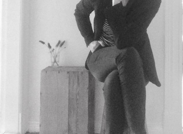 Frau sitzt mit überschlagenen Beinen auf Hocker